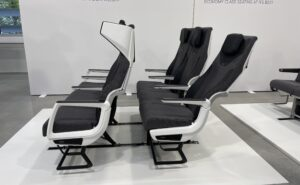 A showcase of the CL3810. Two seat triples - in shades of grey with white accents - are in view. The winged headrest for privacy is prominent.