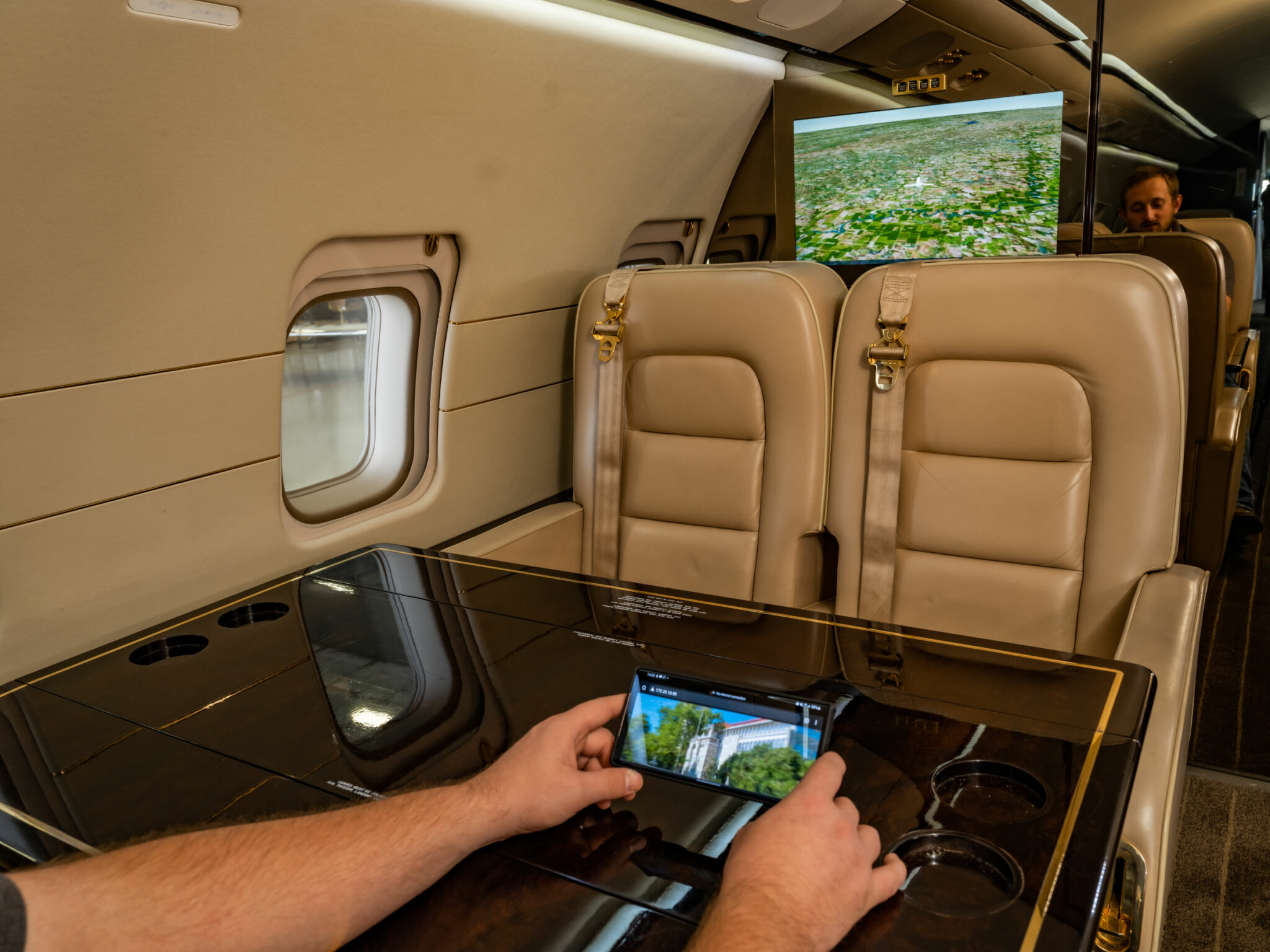 Hands holding a mobile device that is connected to that Goji Geotainment system from Gotham Studios on a Bombardier Challenger 850