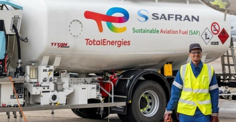 A male employee standing in front of a Safran/Totalenergies fuel tank.