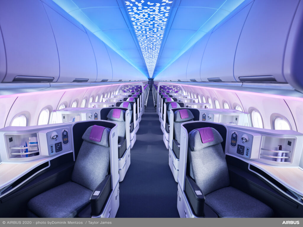 Airbus Airspace image of Business Class seating. A lot of blue and purple highlight the interior.