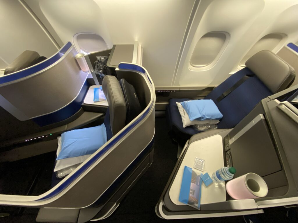 Up close photo of United Airlines' 767-300ER Polaris Business Class seat with the bedding, including cooling pillow, waiting for the passenger on the seat