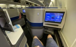 United Airlines' 767-300ER Polaris business class seat with a man's knees showing plenty of space. The IFE screen is seen prominently in this photo