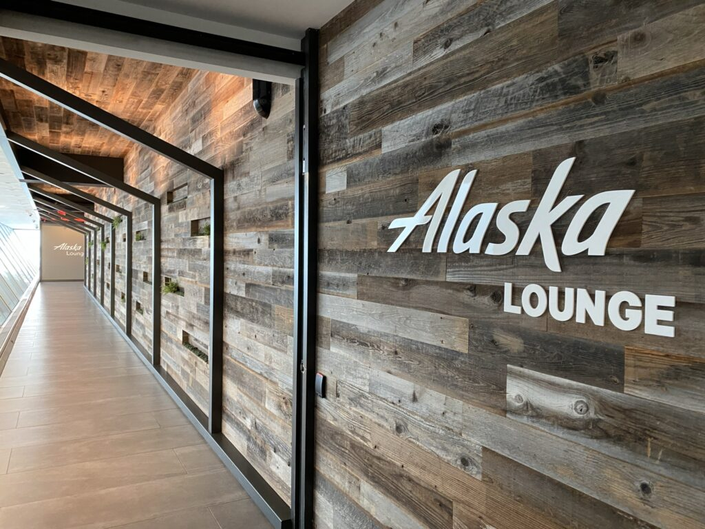 """Alaska Airlines' lounge entrance at JFK, with modern wood paneling on the walls and ceiling, and white lettering for """"Alaska Lounge"""""""