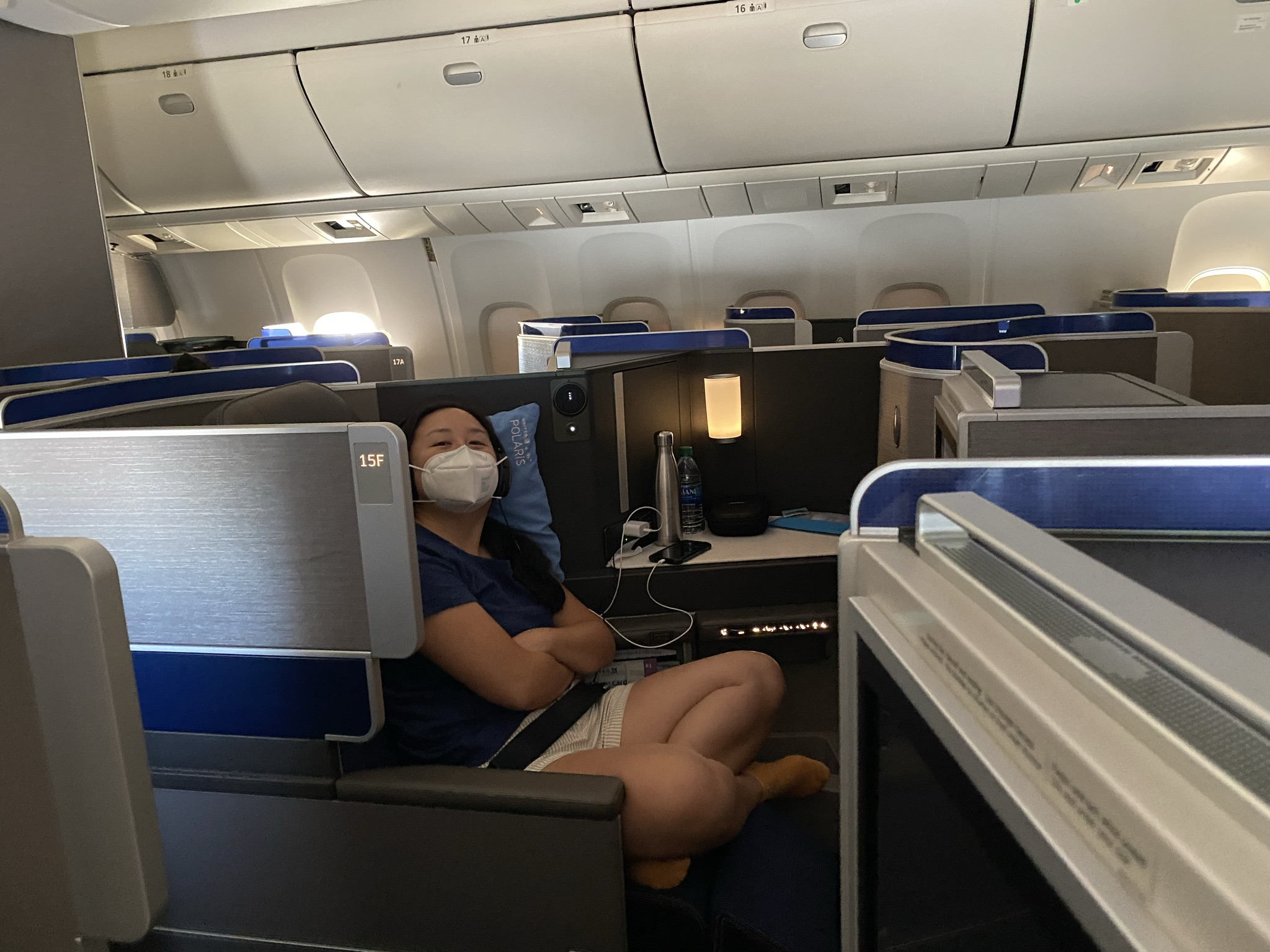 United Airlines' 767-300ER Polaris Business Class seat with a cross-legged female occupant in a white mask