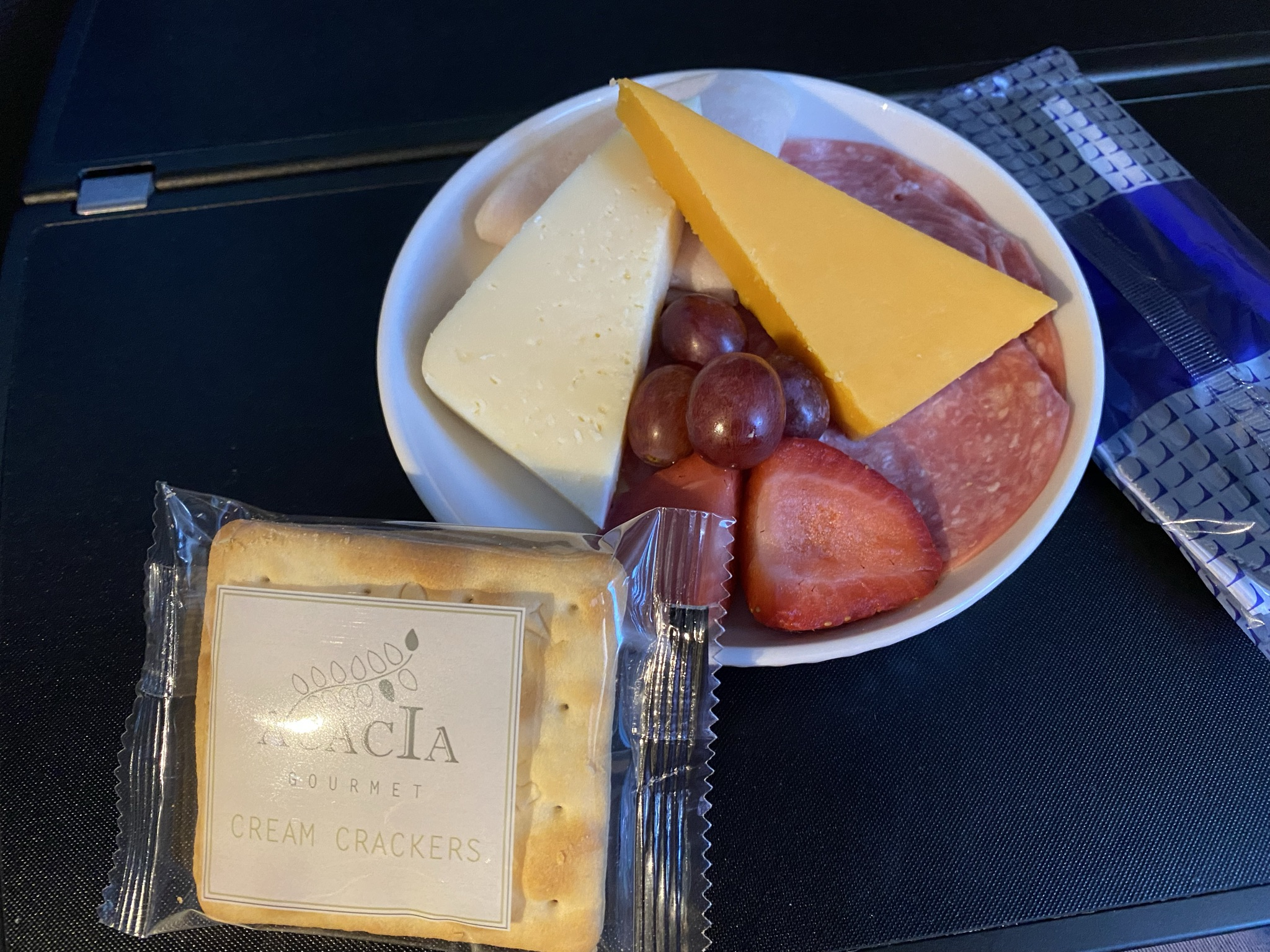 Snack served on the United Airlines 767-600ER including cheese, crackers, meat and some grapes