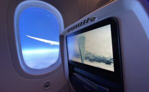Flying onboard the United 787-9; this image shows the seatback IFE and a view of the wing out the window with a beautiful blue sky backdrop