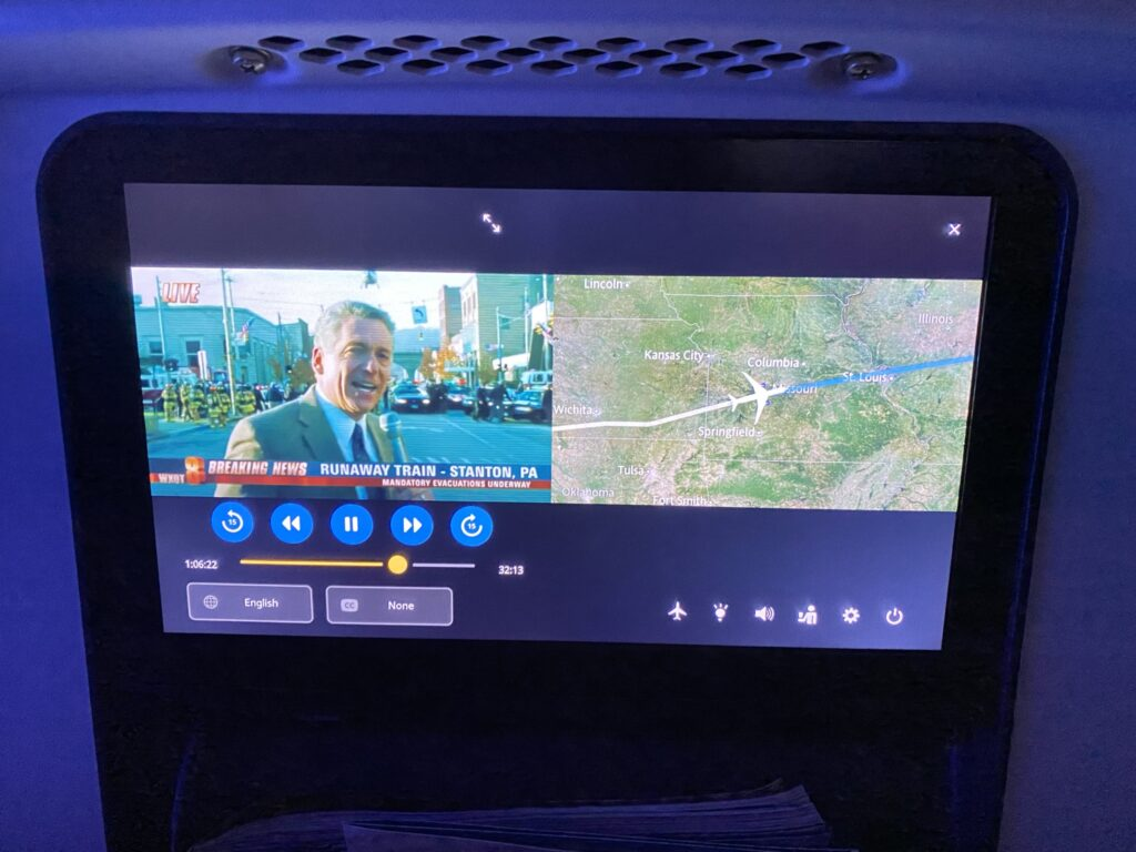 Panasonic seatback IFE on United Airlines 787-9 economy class seat. Showing the news on one half of the screen and a moving map on the other.