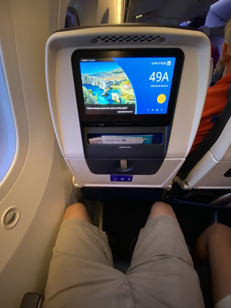 A man's lap and legs are shown sitting in the United Airlines Boeing 787-9 economy class seat. You can also see the embedded IFE in the seatback.