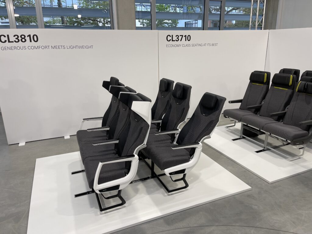 A showcase of the CL3810. Two seat triples - in shades of grey - are in view. The winged headrest for privacy is prominent.