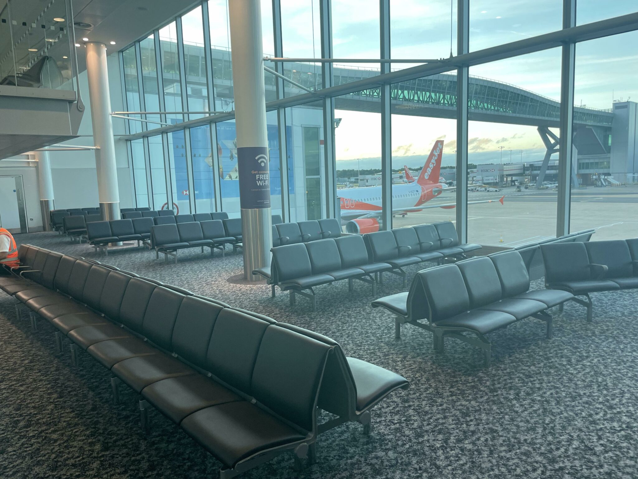 Empty gate area at London Gatwick Airport. The tail of an easyJet aircraft is visible out the window.