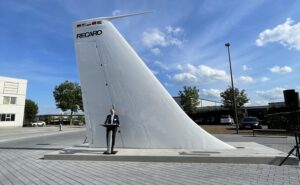 A large aircraft tail monument with a man standing in front of it at a podium.