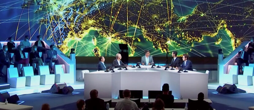 A screenshot of the Airbus summit with a large map of Europe seen behind a group of executives at a table