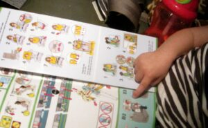 Small Child sitting in an aircraft seat looking at the safety card.