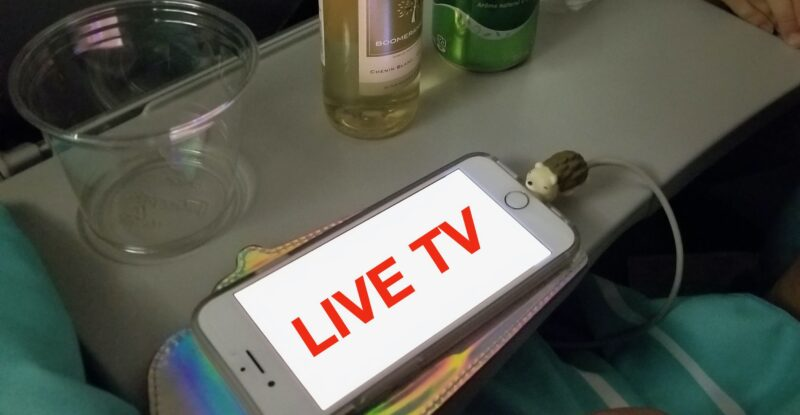 A smartphone laying on an aircraft tray table with the words LIVE TV on it