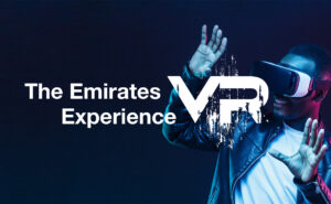 """A man with VR goggles on. Text over top that says """"The Emirates VR Experience""""."""