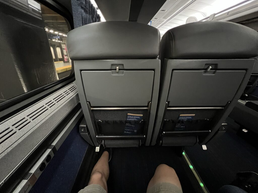 A man's knees showing plenty of space in the Amtrak Business Class seat.