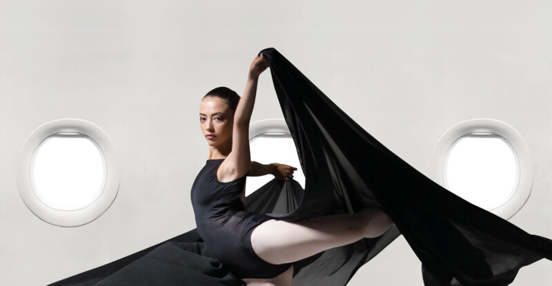 A female dancer in a black bodysuit with a large black sheet doing a arabesque in front of aircraft windows. Image: FACC