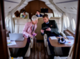 a group of people looking at mobile devices on a business jet.