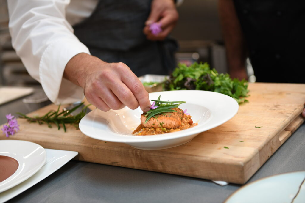 A chef tops off a dish