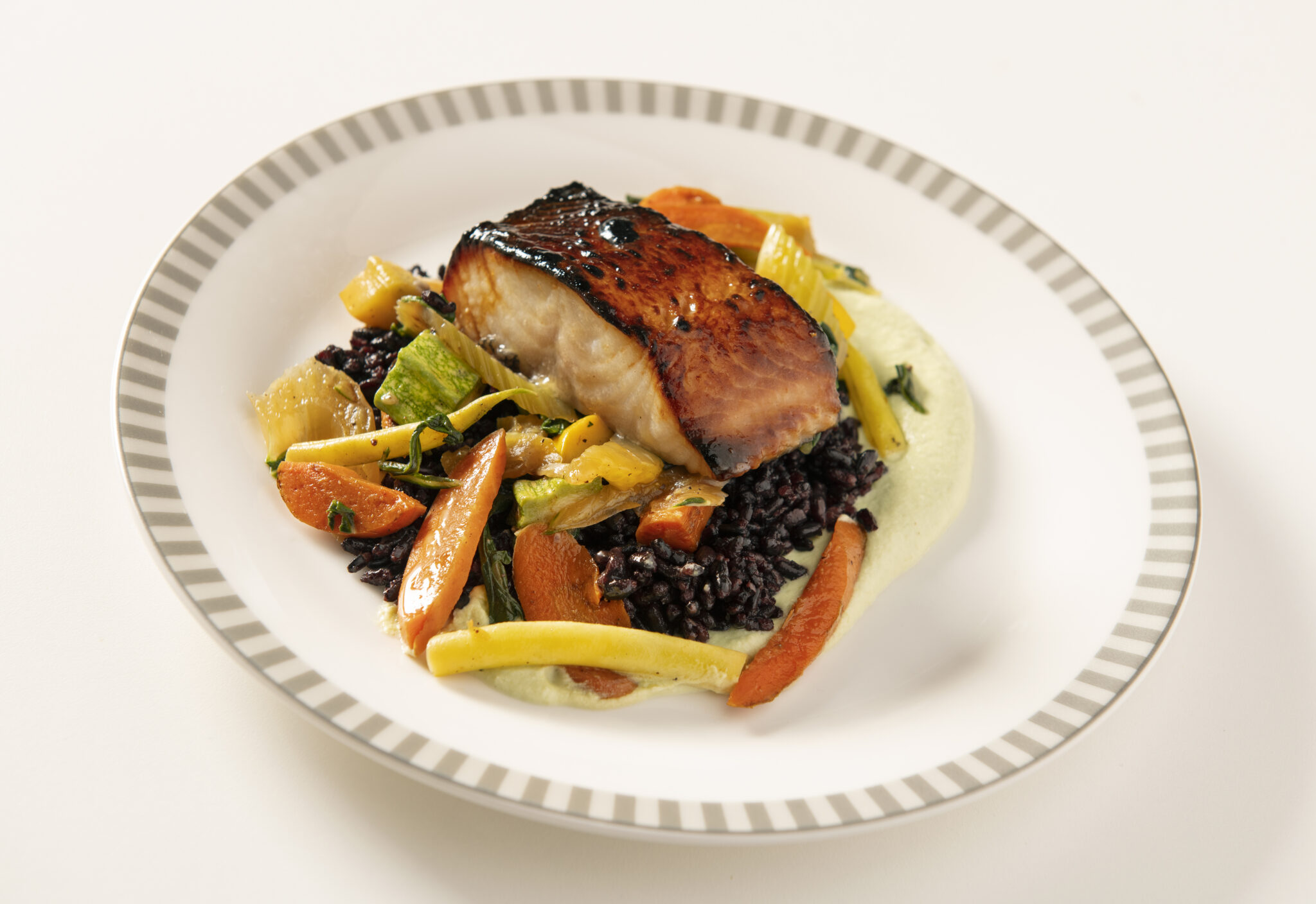 A delectable looking salmon dish, with the filet sitting atop a veggie medley