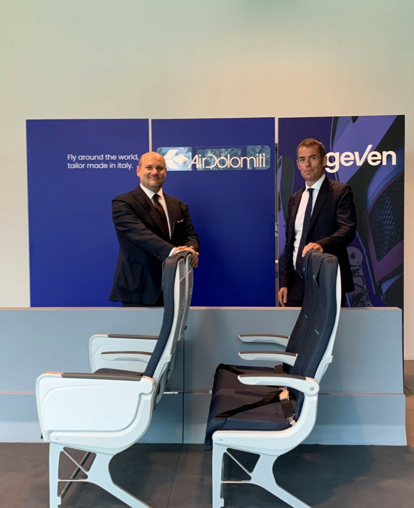 Execs from Air Dolomiti and Geven stand behind The Geven ESSENZA seat model on display.