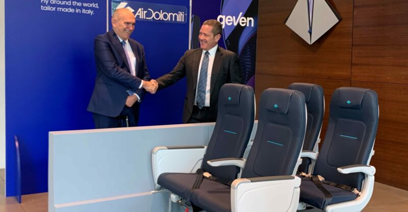 Execs from Air Dolomiti and Geven shake hands. The Geven ESSENZA seat model is displayed in front.