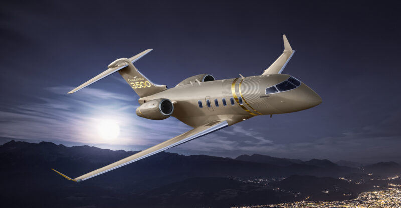Bombardier Challenger 3500 in flight at night over a brightly lit city.